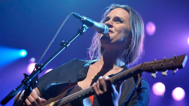 Madeleine Peyroux spielt Gitarre.