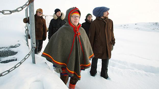 Wimme Saari im bunten Umhang stapft mit drei Männern durch den Schnee
