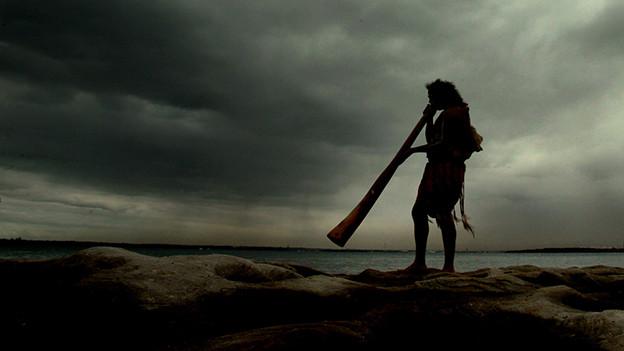 Ein Mann spielt am Meeresufer Didgeridoo