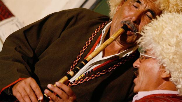 Zwei Männer mit Fellmützen, einer spielt Flöte, der andere singt dazu.