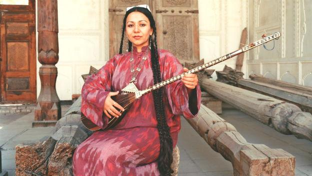 Nodira Pirmatova im Porträt. Sie trägt ein buntes Gewand.