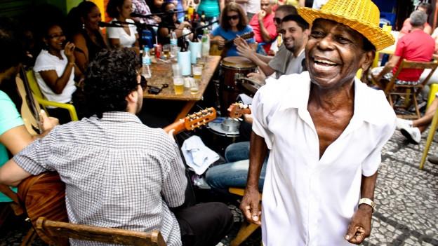 Leute tanzen und machen Strassenmusik. Ein Mann mit gelbem Strohhut im Vordergrund.