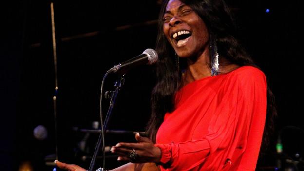 Eine Frau in rotem Kleid singt ausdrucksvoll.