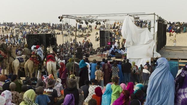 Menschen an einem Festival in der Wüste.