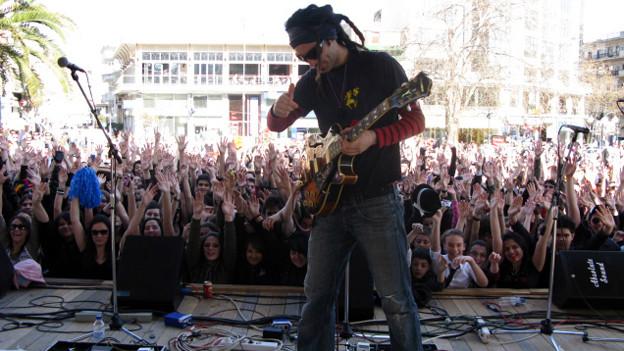 Ein Mann mit Gitarre auf einer Bühne
