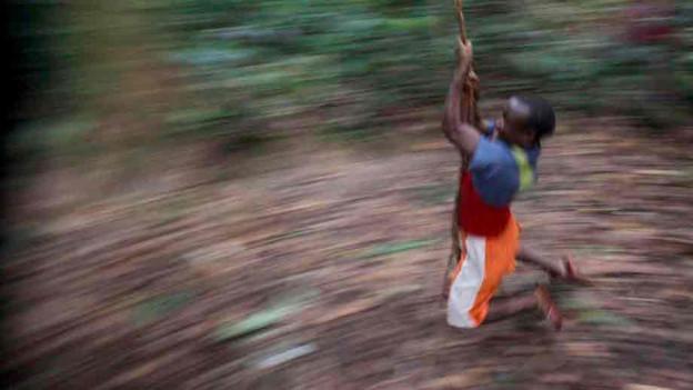 Ein Mann schwingt an einem Seil im Wald.