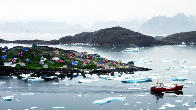 Ein Fischerboot sucht seinen Weg durch die Eisberge vor der Kueste von Kulusuk, Grönland.