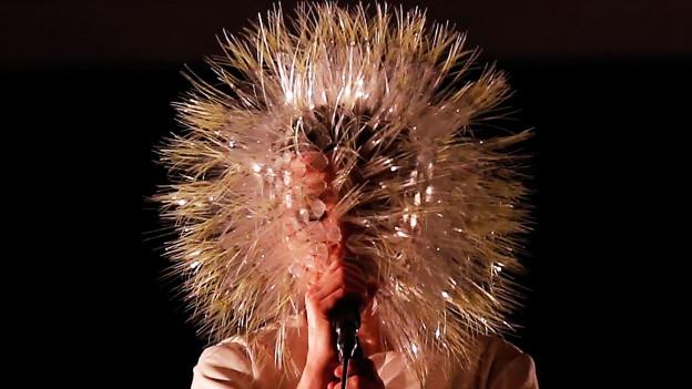 Sängerin Björk trägt bei einen Auftritt eine kugelförmige Maske aus Stacheln.