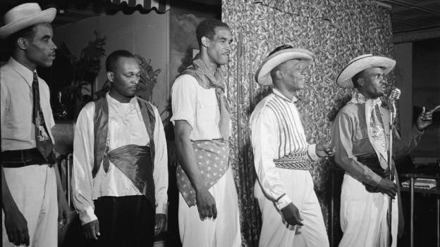 Fünf Männer stehen in einer Reihe. Derjenige auf der rechten Seite hält ein Mikrophon in der Hand.