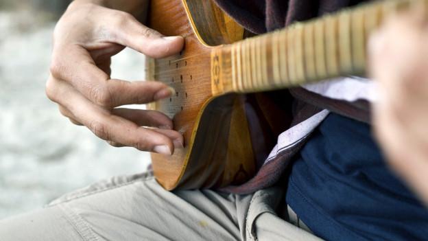 Eine nicht erkennbare Person spielt eine Sitar.