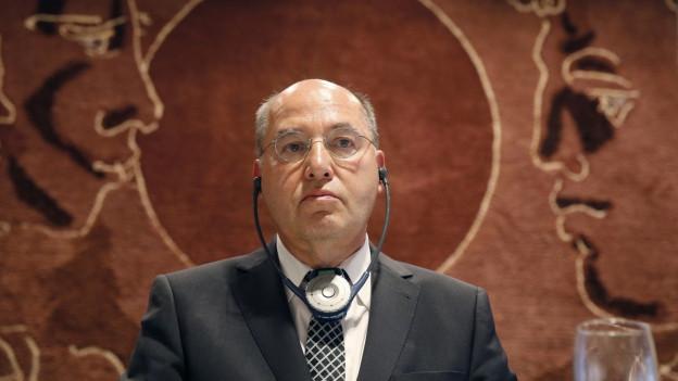 Ein Mann mit Kopfhörer vor einem braunen Wandteppich.