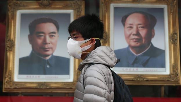 Ein junger Chinese mit Atemschutzmaske geht an zwei grossen Fotos vorbei. Die eine zeigt Mao Zedong.
