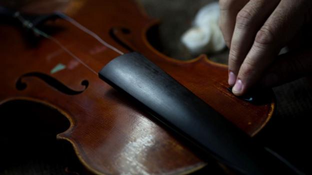 Hand streicht über eine Geige.