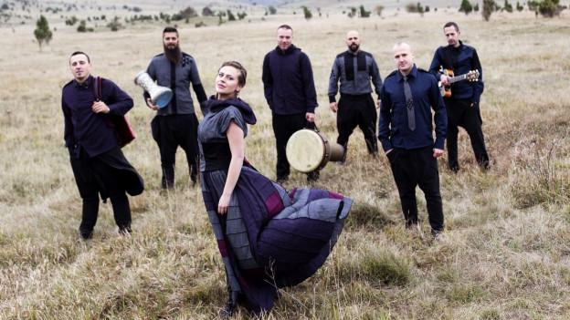 Sechs dunkel gekleidete Männer stehen auf einer Wiese, in ihrer Mitte ist eine Frau mit Kleid und langem Haar.