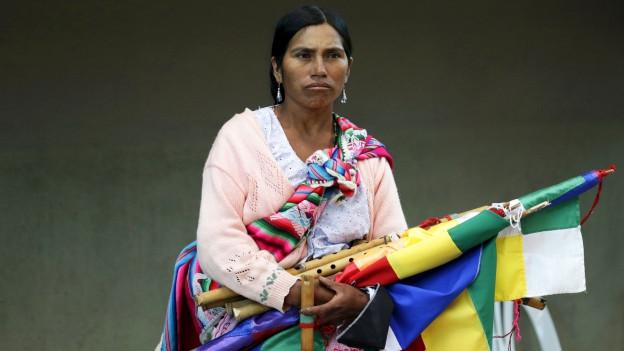 Eine Frau hält diverse Musikinstrumente und Banner.