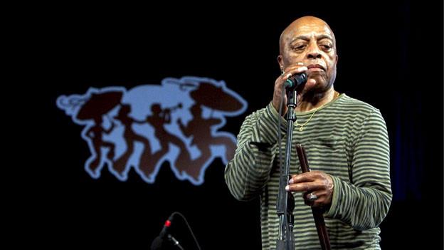 Mann auf Bühne mit Mikrofon.