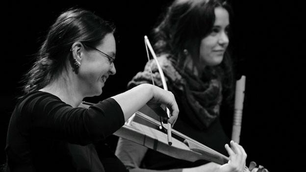 Man sieht eine Frau, Violine spielen. Im Hintergrund ist eine Frau, die Blockflöte spielt.