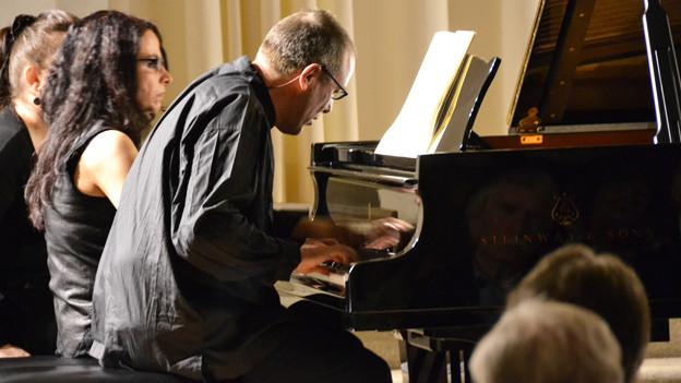 Das Bild zeigt das Künstlerduo Alexander Lonquich und Christina Barbuti, wie es an einem Klavier sitzt und ein vierhändiges Stück spielt.