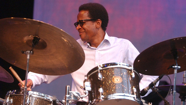 Mann an Schlagzeug.