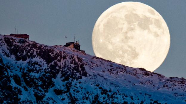 Ein Mond hinter einem Berg.