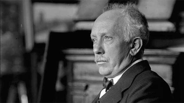 Schwarzweissfoto, Strauss sitzt mit enrstem Gesicht auf einem Stuhl