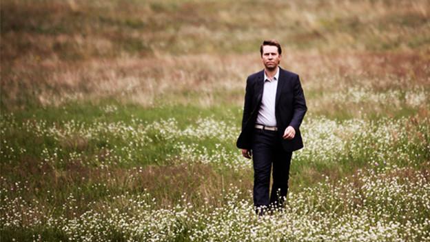 Leif Ove Andsnes in einer Blumenwiese.