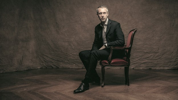 Ein Mann sitzt auf einem Stuhl in einem verdunkelten Raum: Ein Portrait von Sébastien Daucé.