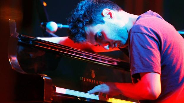 Ein junger Mann spielt Klavier.