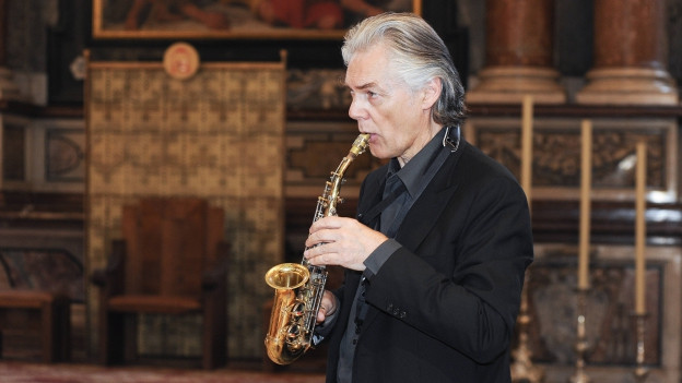 Jan Garbarek in einer Kirche und spielt Saxophon.