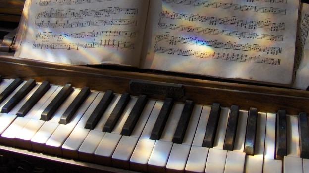 Schatten fällt auf ein altes Klavier