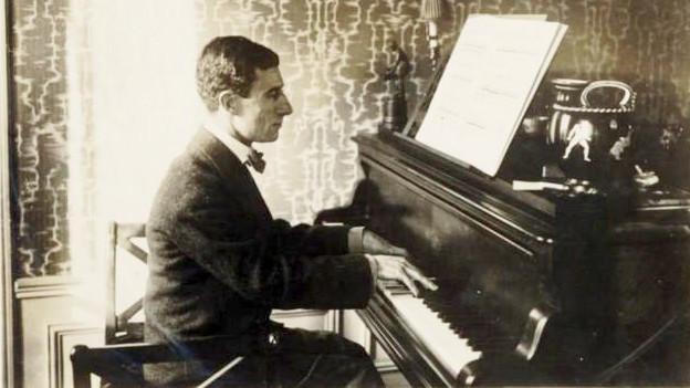 Schwarzweiss-Fotografie eines Mannes am Klavier.
