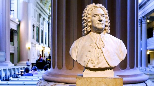 Eine weisse Statue Bachs auf einem Sockel, dahinter eine Säule.