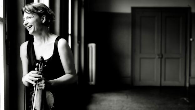 Eien Frau lehnt an ein Fenster, in der Hand hält sie eine Geige.