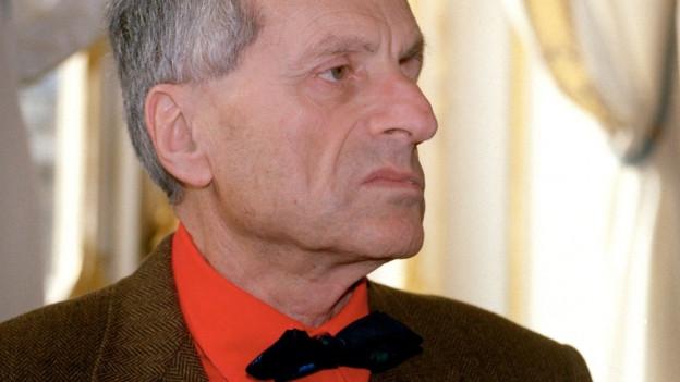 Ein Mann im roten Hemd mit Fliege und markanter Nase im Profil gesehen.