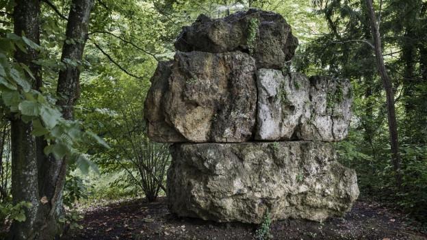 Drei grosse, übereinandergeschichtete Steine in eienm Wald