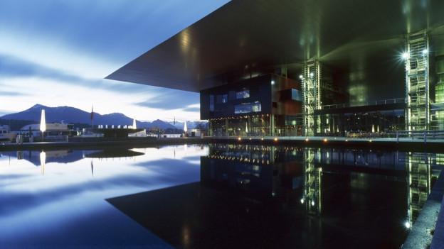 Ein grosses Gebäude am See, es ist am Eindunklen, Lichter leuchten.