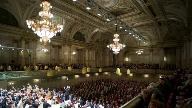 Ein grosser Raum mit Kronleuchtern; Publikum auf der Galerie runherum und unten, vorne ein Orchester.