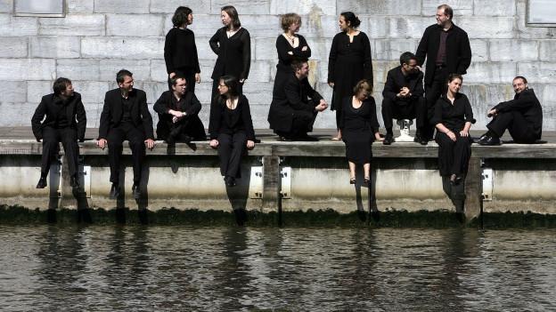 Les Muffati stehen an einem Ufer.
