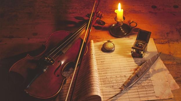 Notenblatt mit Schreibfeder im Kerzenlicht.