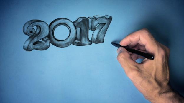 Eine Hand zeichnet die Zahl 2017.