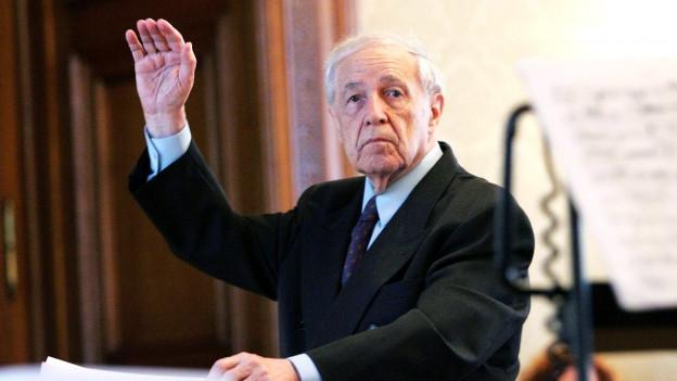 Ein älterer Herr, die linke Hand erhoben, die rechte hält ein Notenblatt.