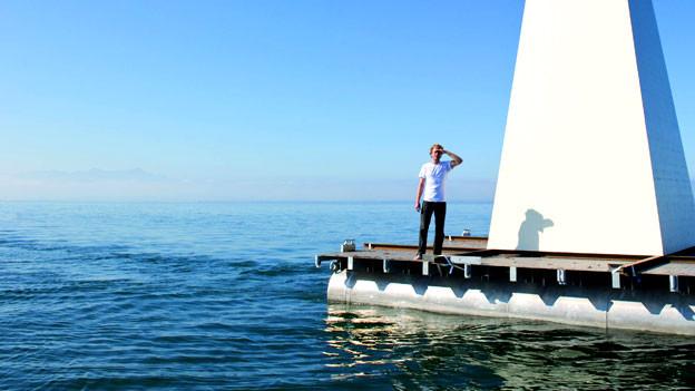 Mann auf Floss mit Leuchtturm auf See.