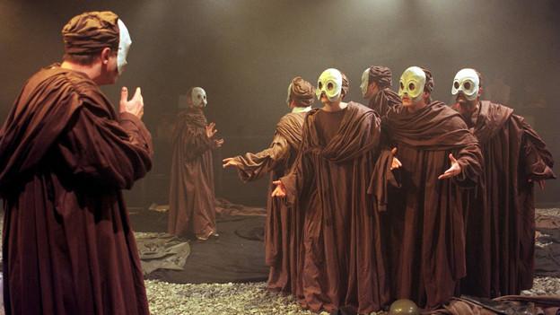 Auf einer Bühne stehen mehrere Menschen in braunen Kutten mit Masken mit grossen Augen.