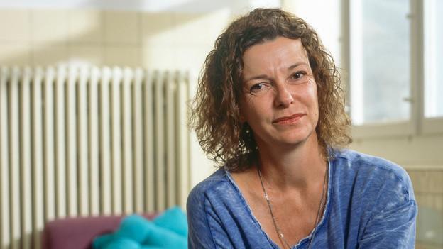 Milena Moser in ihrer Wohnung. Sie trägt ein blaues T-Shirt. Im Hintergrund ein Fenster und Radiatoren.