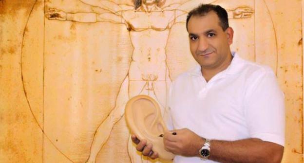 Wissam Charaf mit einem Modell eines Ohres in der Hand.