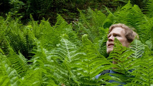 Jan Bollmann umgeben von einer Pflanze.
