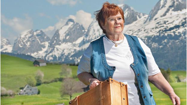 Eine Frau mit einem Koffer läuft über eine Wiese.