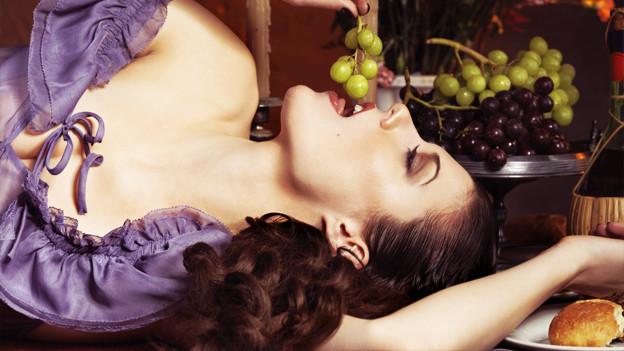 Eine Frau liegt leicht bekleidet auf einem schön gedeckten Tisch.