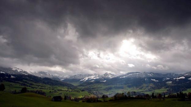 Ein wolkenverhangener Himmel über Häusern und Wiesen im Toggenburg.