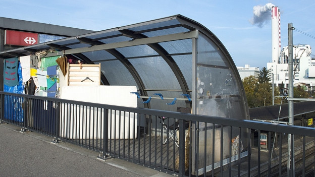 Ein Obdachloser hat sich in einem nicht genutzten Velounterstand auf einer Brücke eine Unterkunft eingerichtet.